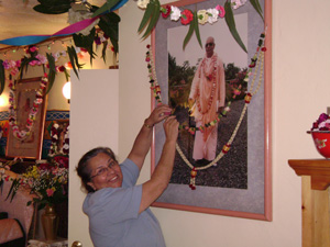 Diksavati Didi garlanding Srila Gurudev's picture in the Temple room.