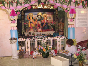 Young Ramananda Prabhu reads from Srimad Bhagavad Gita in front of Their Lordships while the decorations are being prepared.