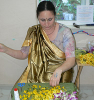 The garland seva is ongoing, here Krishnapriya Didi sews garlands for the small Deities.