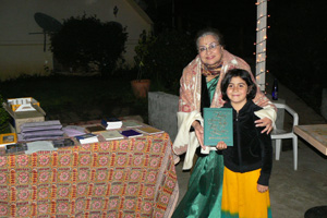 Diksavati Didi gets assistance from young Radha Dasi at the book table.
