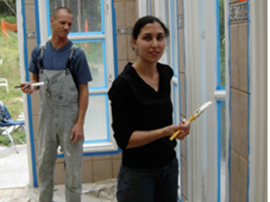 Giridhari Prabhu and Sara painting the trim around the windows.