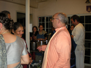 Sripad Janardan Maharaj helps arrange seating for special guests.