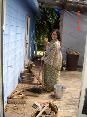 Madhurapriya Didi cleans the flower porch and firewood area.