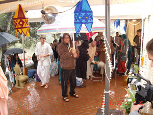 Phalguni Krishna Prabhu holds his large umbrella to offer shelter to the devotees offering flowers.
